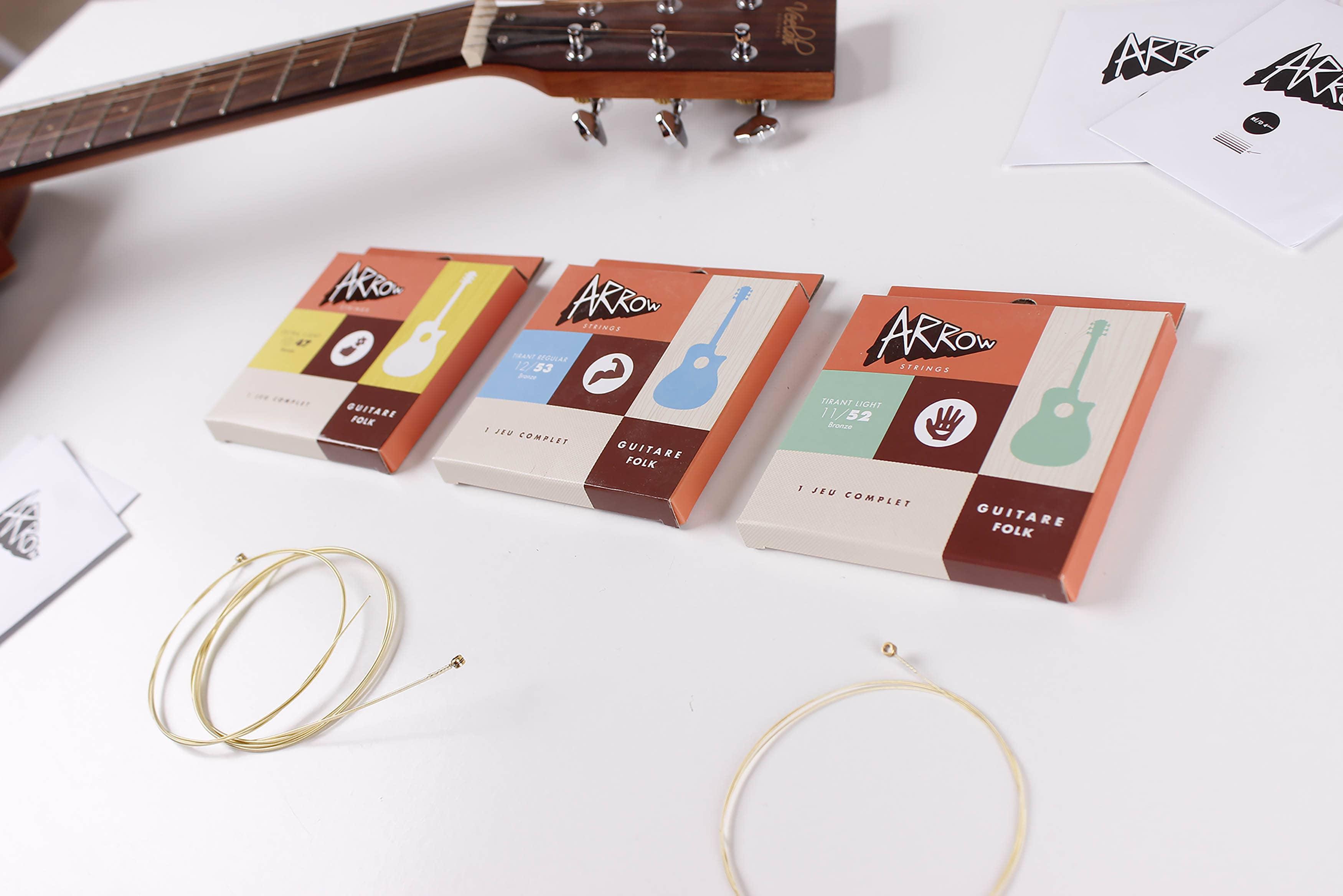 Jeux de cordes Arrow. 3 jeux de cordes pour guitare folk alignées sur une table blanche à coté d'une guitare. Quelques cordes sont sorties autour des pochettes.
